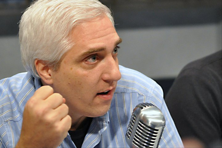 Headshot of Dr. Steven Novella with a microphone